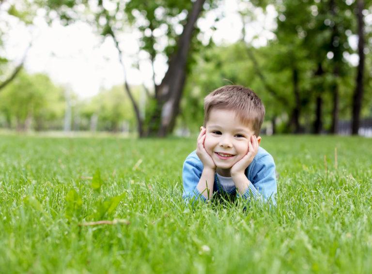 Little boy smiling in grass