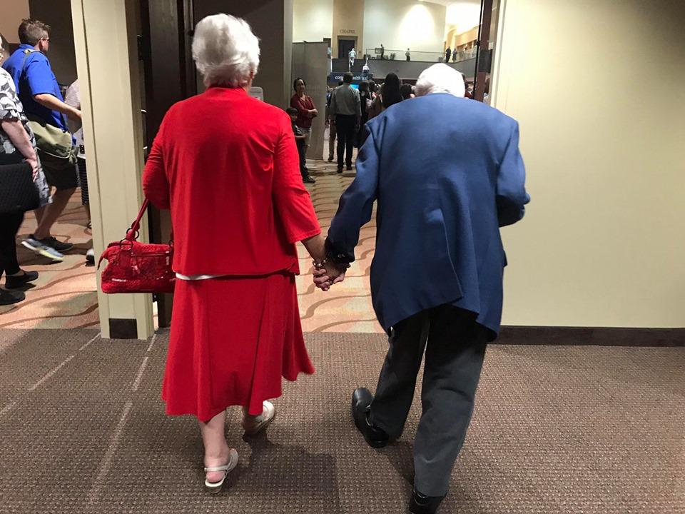 Elderly couple holding hands walking