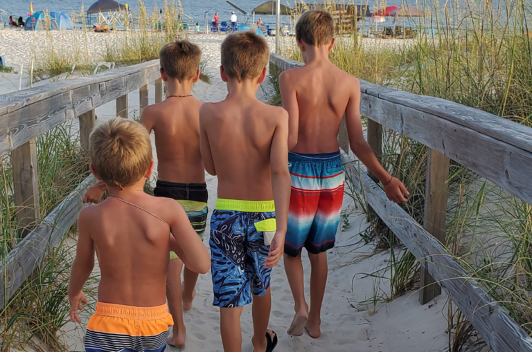 Four boys walking to beach