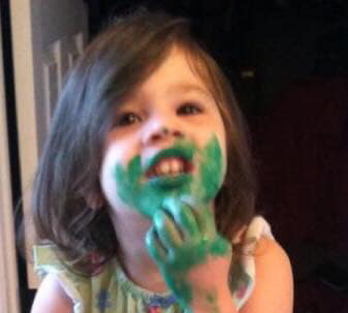 Child with green paint on face