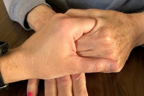 Woman holding elderly mother's hand hand