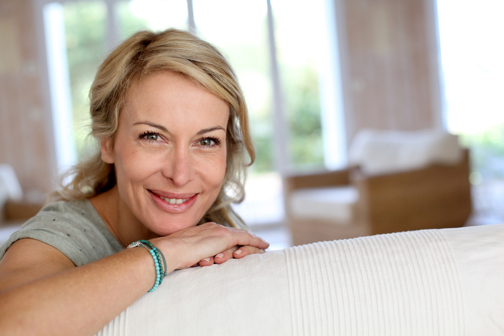 middle aged woman smiling on couch