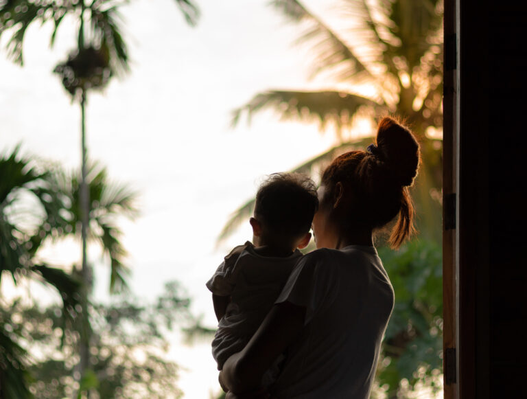 Woman holding baby looking out window
