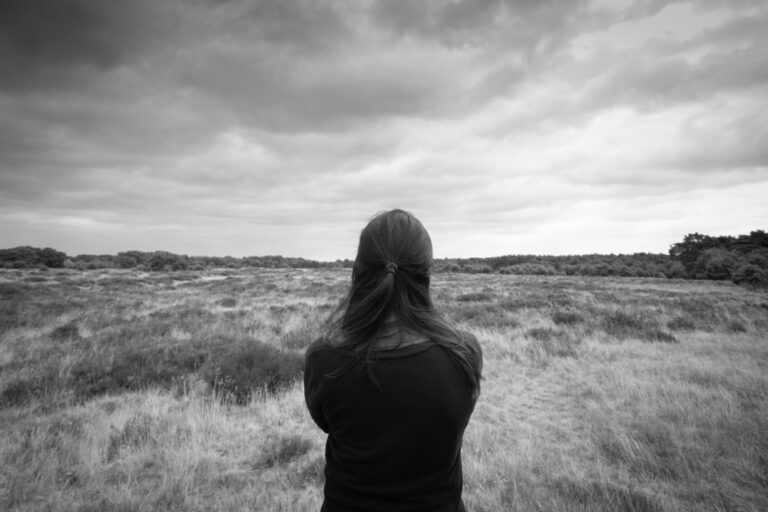 Woman looking out at field black and white