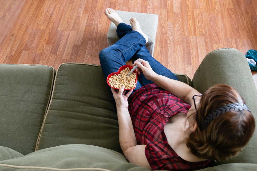 Woman on couch eating Cheerios