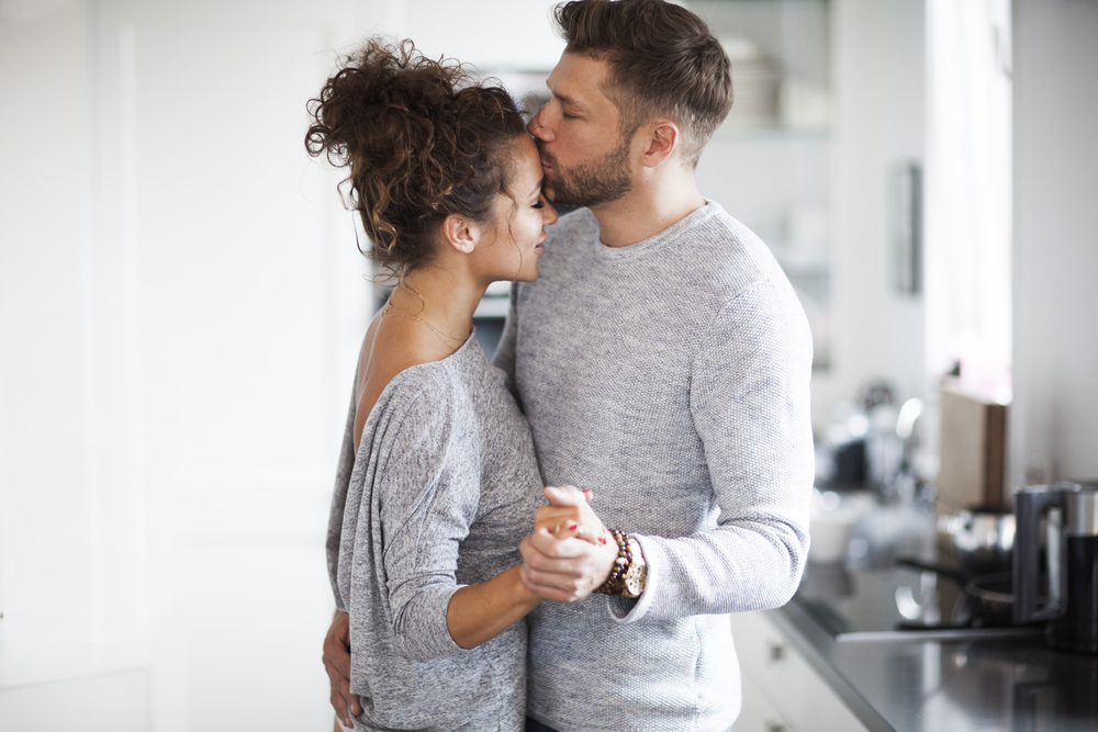 Husband and wife dance in kitchen