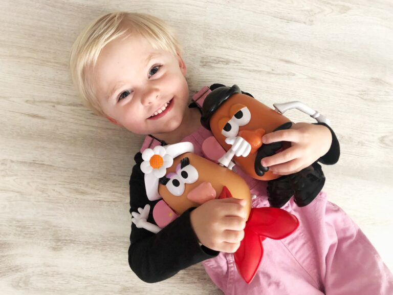girl holding Potato Head toys