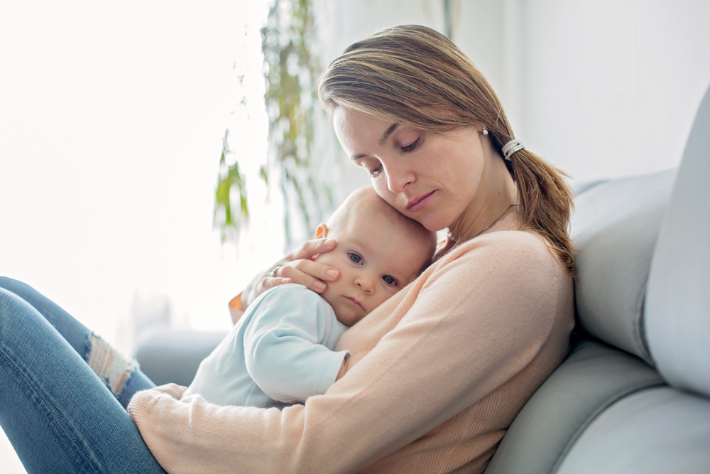 tired mother holding baby on a couch