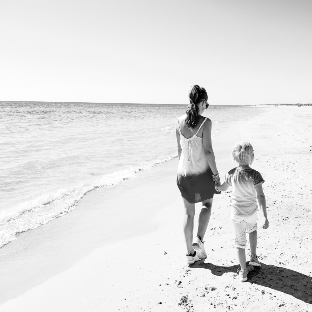 Mom and child walking on beach