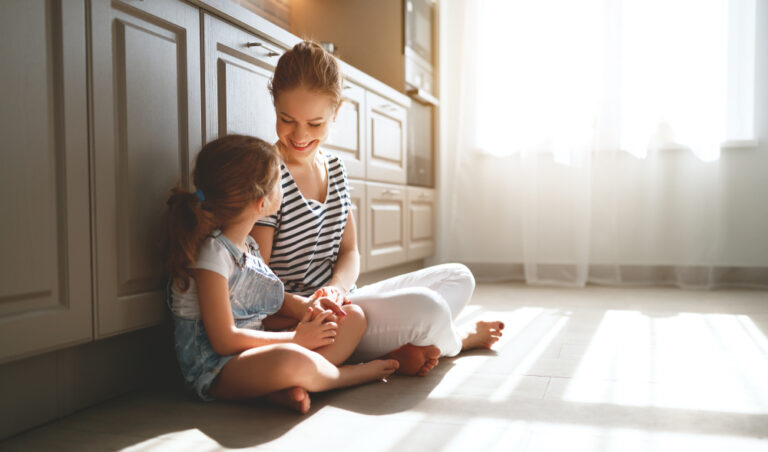Mother and daughter sitting on floor