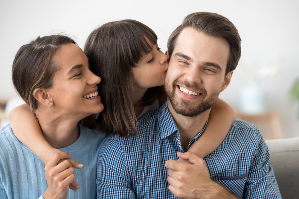 Family kissing dad