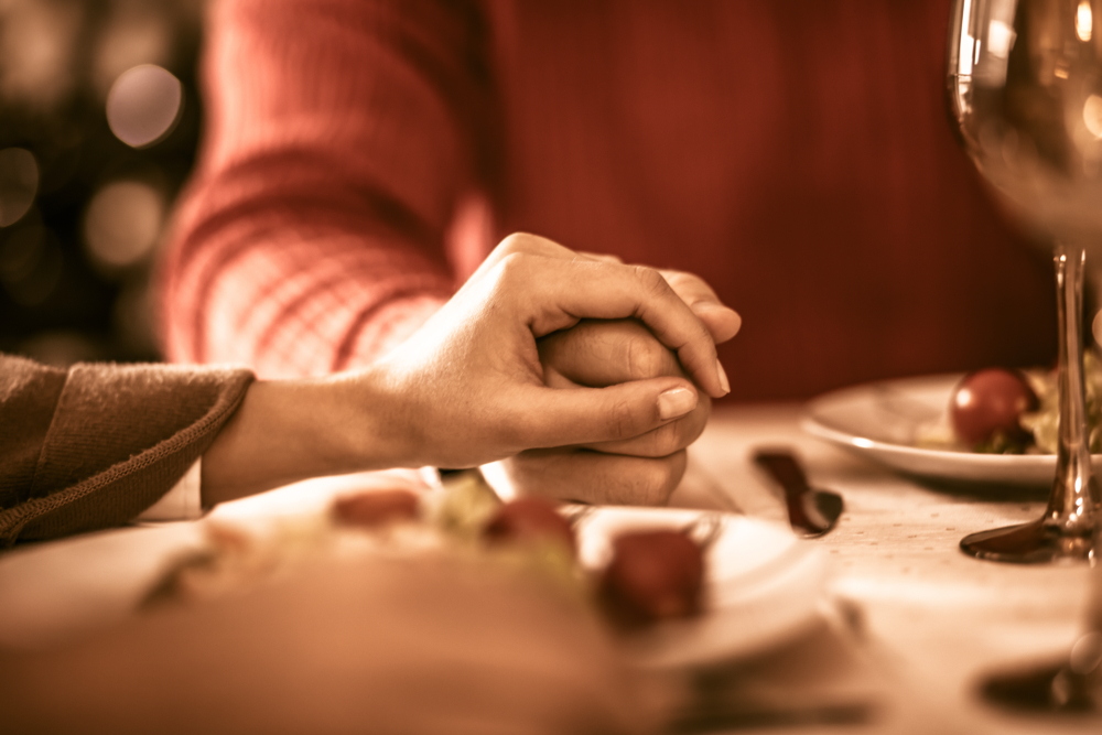 people holding hands at holiday table