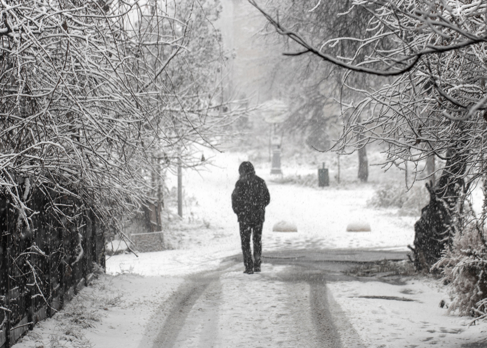 Man walking alone on snowy road