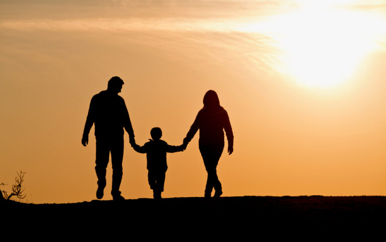 Family walking in sunset silhouette