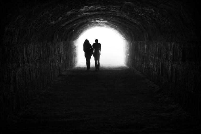 couple walking through tunnel in the dark
