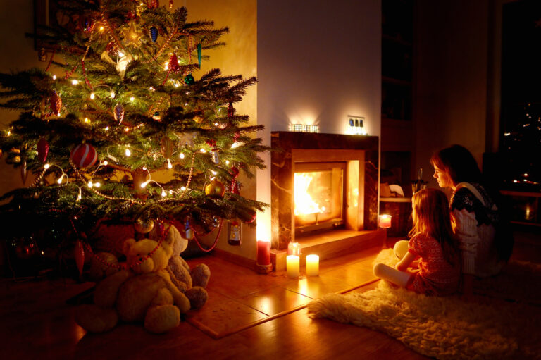 Family in front of fire and CHristmas tree