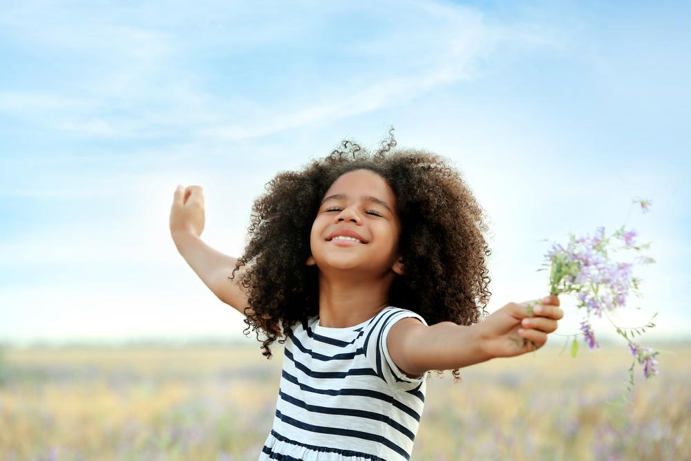 Happy little girl holding flower