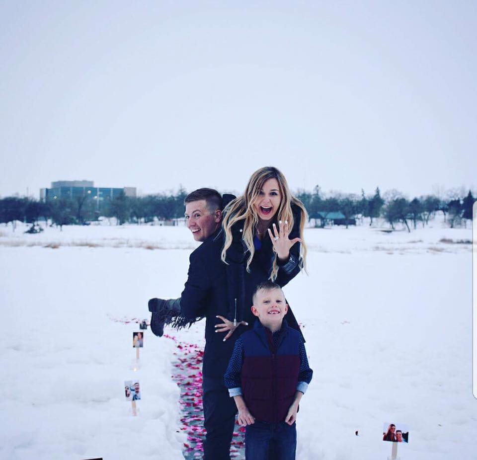 Engaged woman with man and his son in the snow