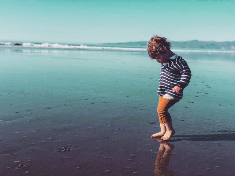 Little boy jumping on beach