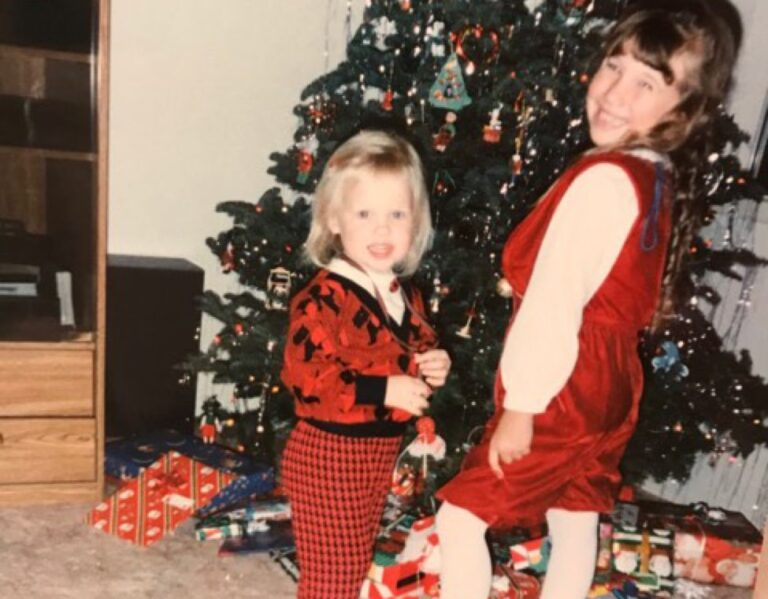 Two little girls by a Christmas tree in the 90s