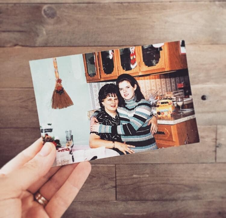 Woman's hand holding photo of mother and grown daughter