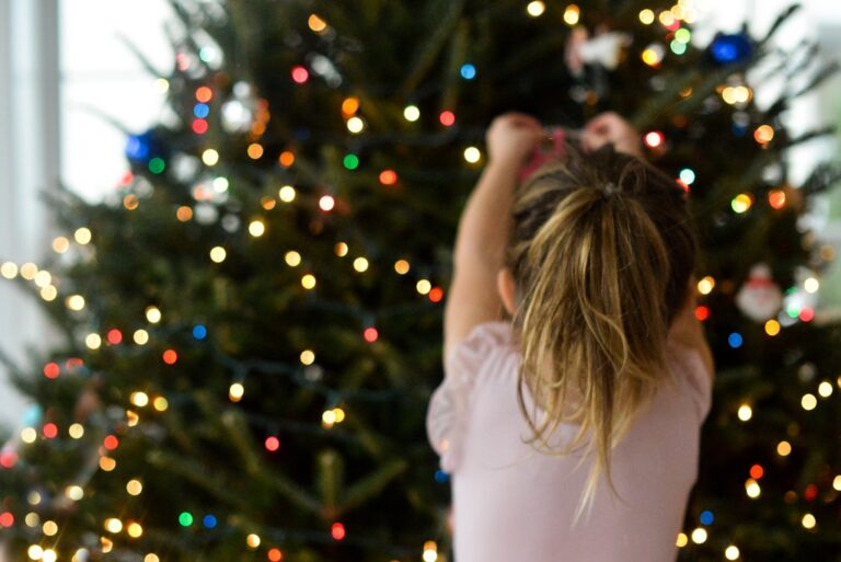 Girl hanging Christmas ornaments on tree