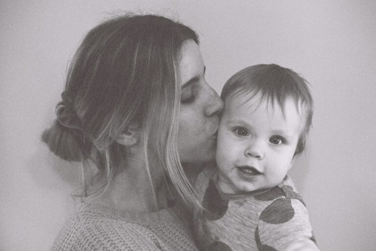 Mother kissing baby, black-and-white photo