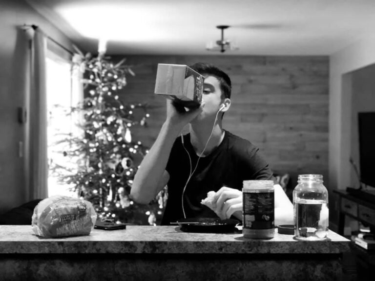 Teenage boy drinking juice from carton at home