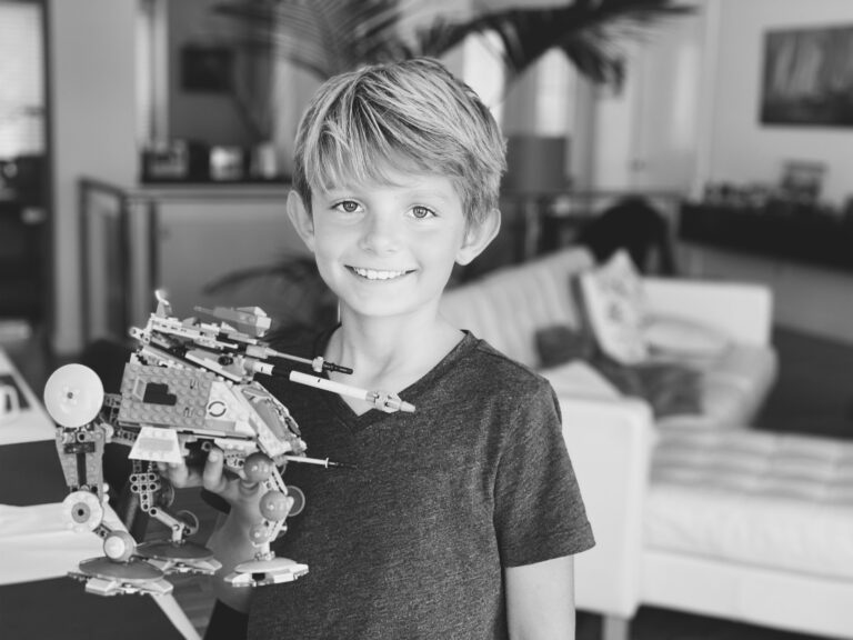 Little boy holding LEGO creation