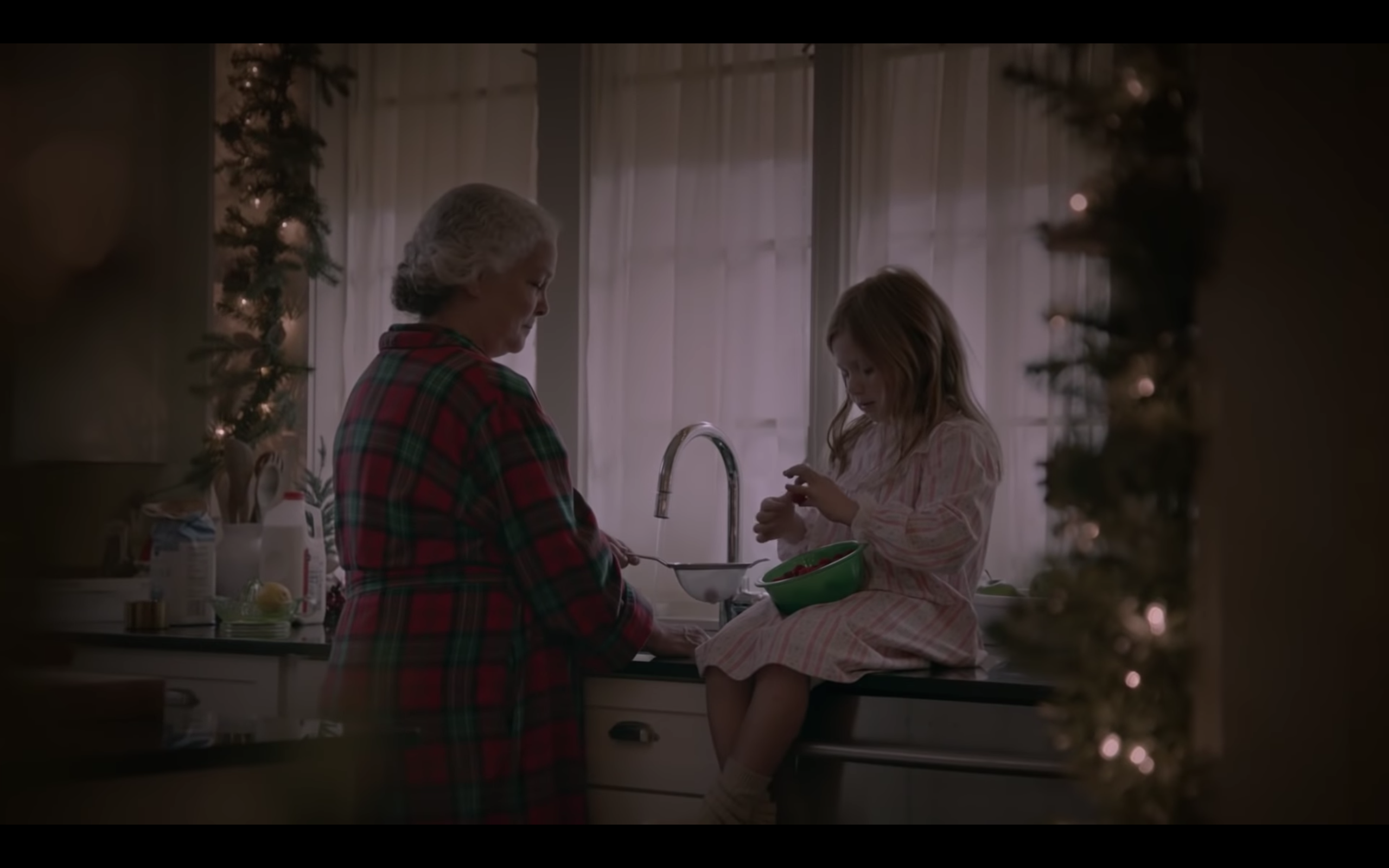 Grandma and granddaughter on Christmas morning in kitchen