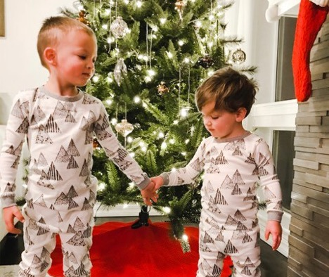 Young brothers hold hands by Christmas tree
