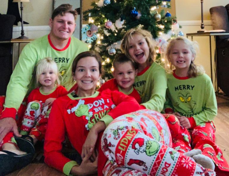 Family by christmas tree in pajamas
