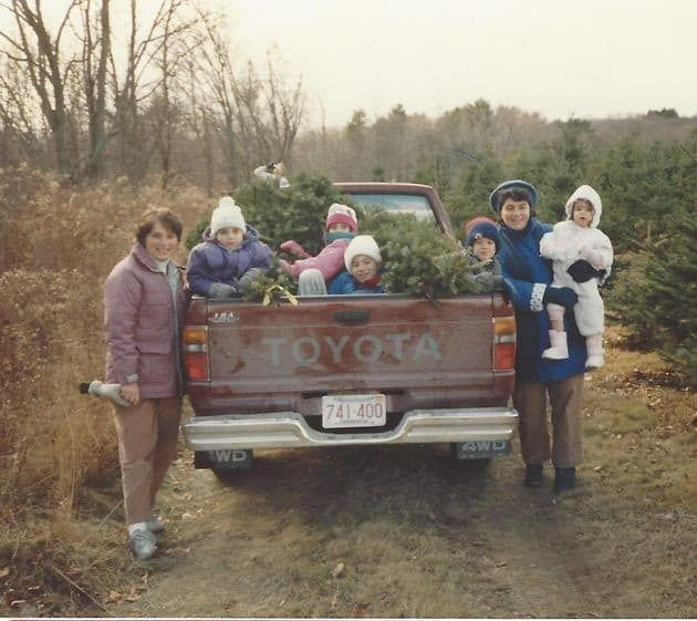 Family gathered around a truck with a Christmas tree, color phogo