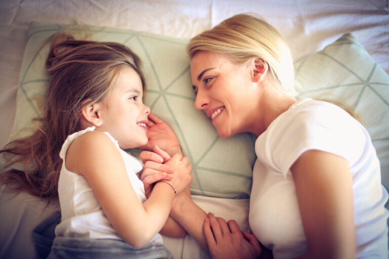 Mother and daughter in bed smiling