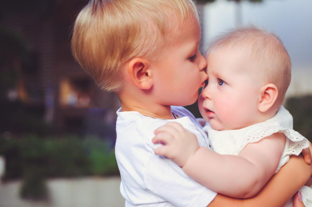 Siblings brother and sister kissing