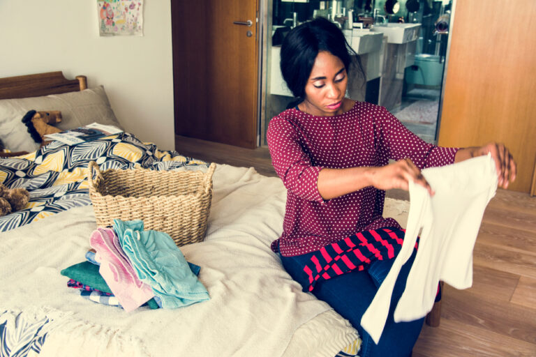 Woman folding clothes in kid's room