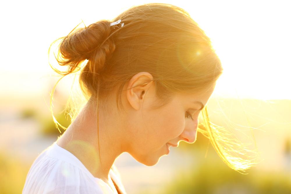 Woman in sunlight looking down