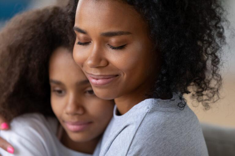 Mom hugging teen daughter