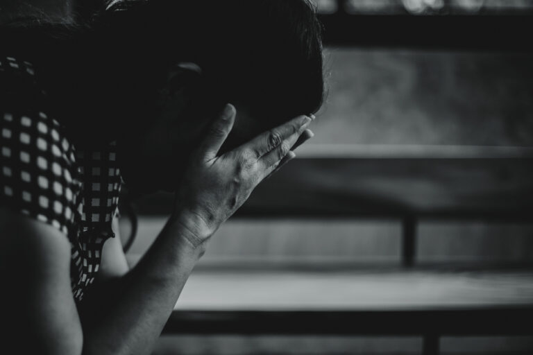 Sad woman head in her hands, black and white photo