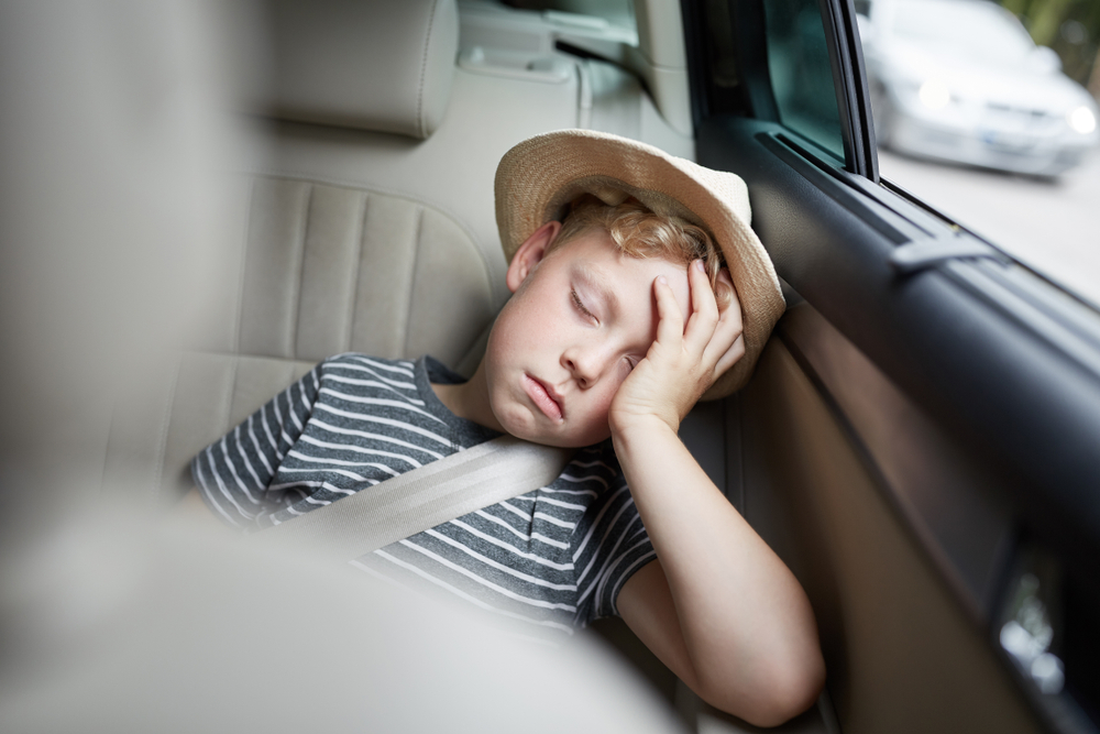 little boy in backseat of car asleep