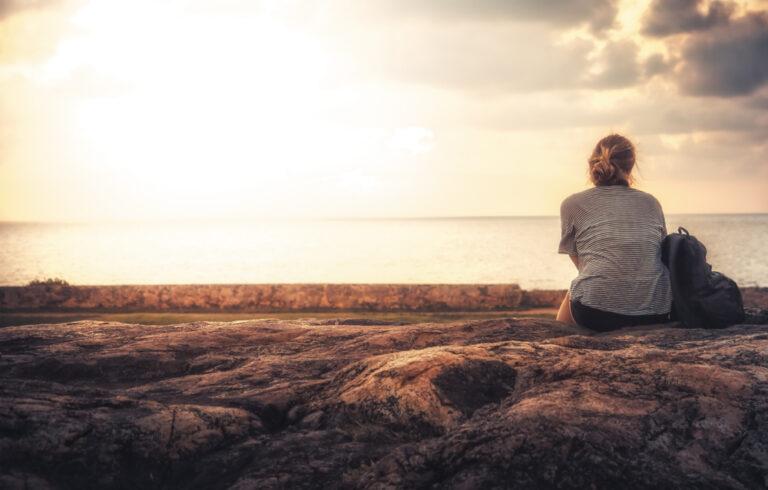 Woman sitting alone beach
