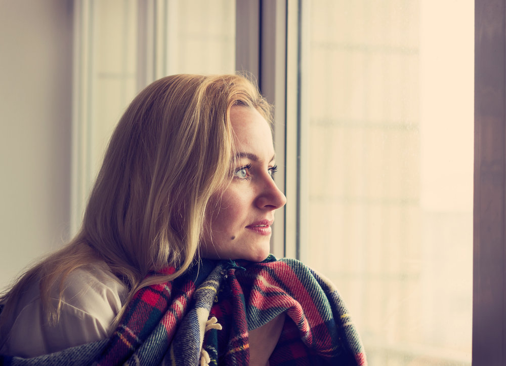 Woman with blanket looking out window