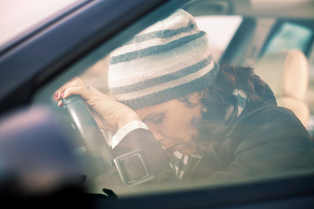 Woman in the car leaning head on wheel