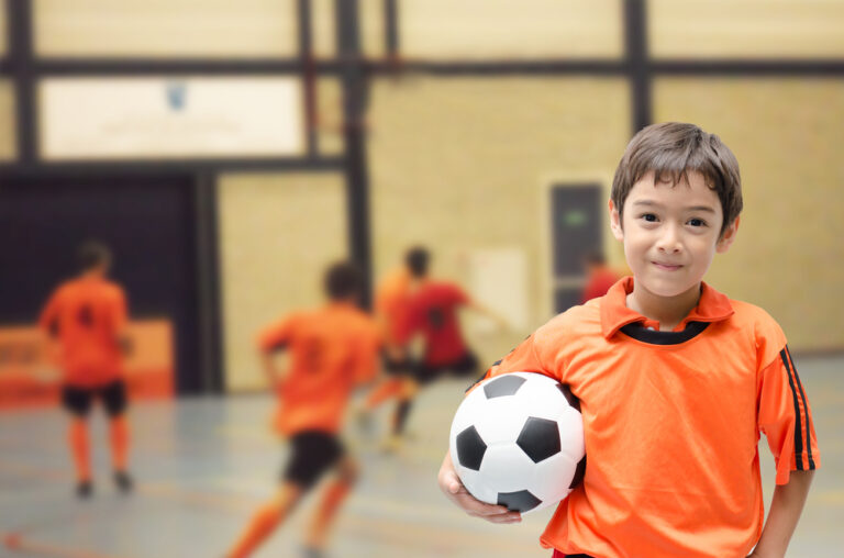 Little boy holding soccer ball