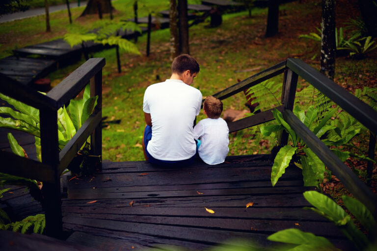 Man and young boy sitting on steps of deck