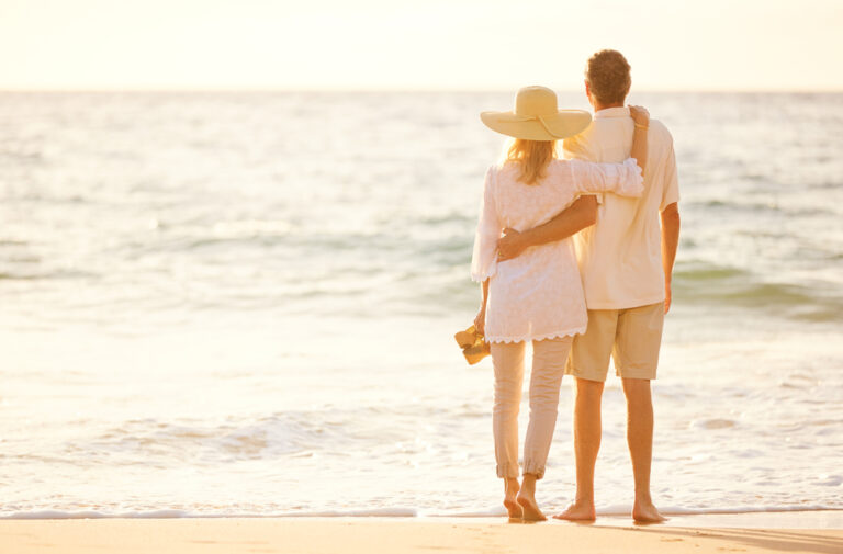 Middle aged couple on the beach looking at sea