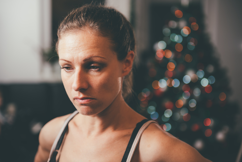 Sad woman with Christmas tree in backgroud
