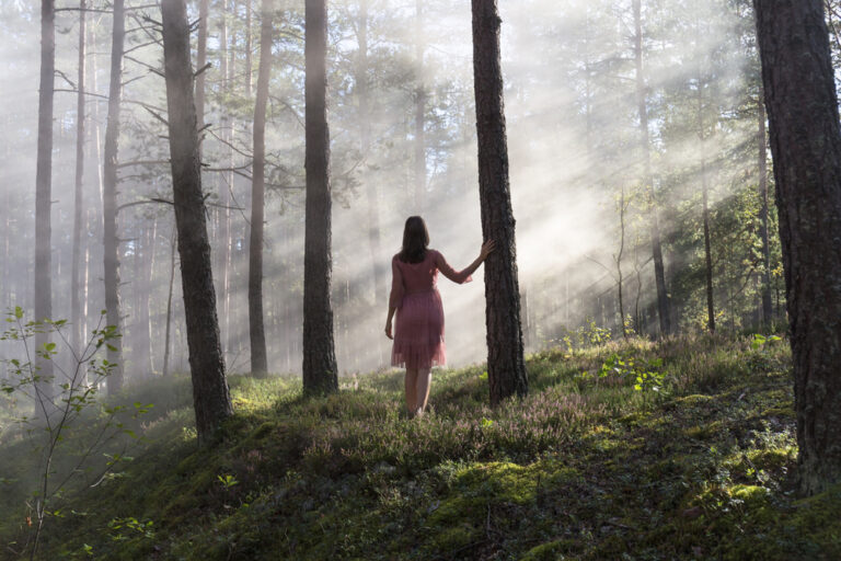 Woman in woods with sunlight in trees