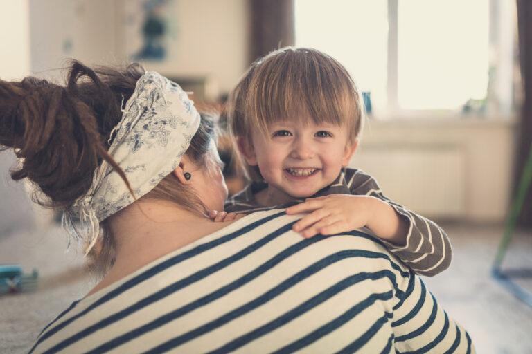 Little boy looking over mom's shoulder smiling