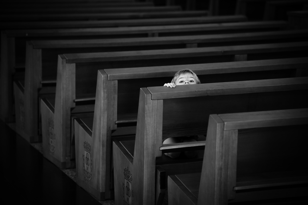 Little boy hiding in church pew